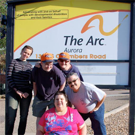 Arc Members pose in front of Arc of Aurora sign